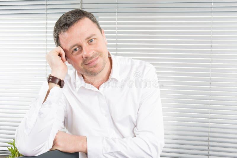 όμορφο άτομο επιχειρηματιών στην αρχή με το άσπρο χαμόγελο πουκάμισων στοκ φωτογραφία