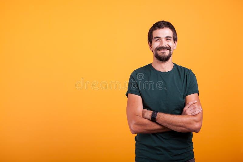 Όμορφο άτομο με τα όπλα του που διασχίζονται χαμόγελο στη κάμερα στοκ εικόνα με δικαίωμα ελεύθερης χρήσης