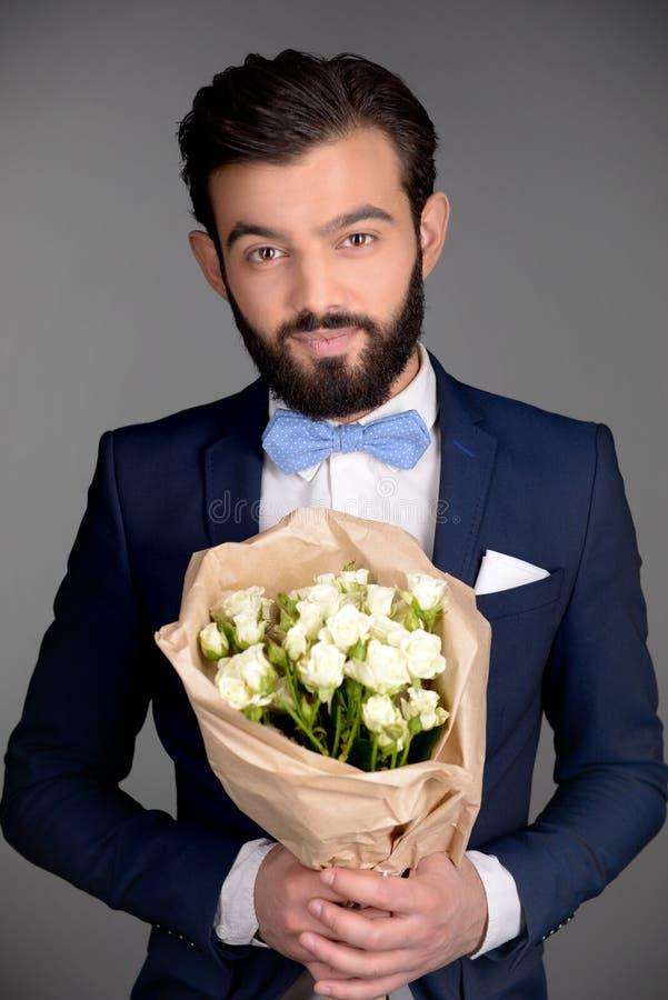 Όμορφο άτομο με την ανθοδέσμη εκμετάλλευσης γενειάδων των λουλουδιών στοκ εικόνα