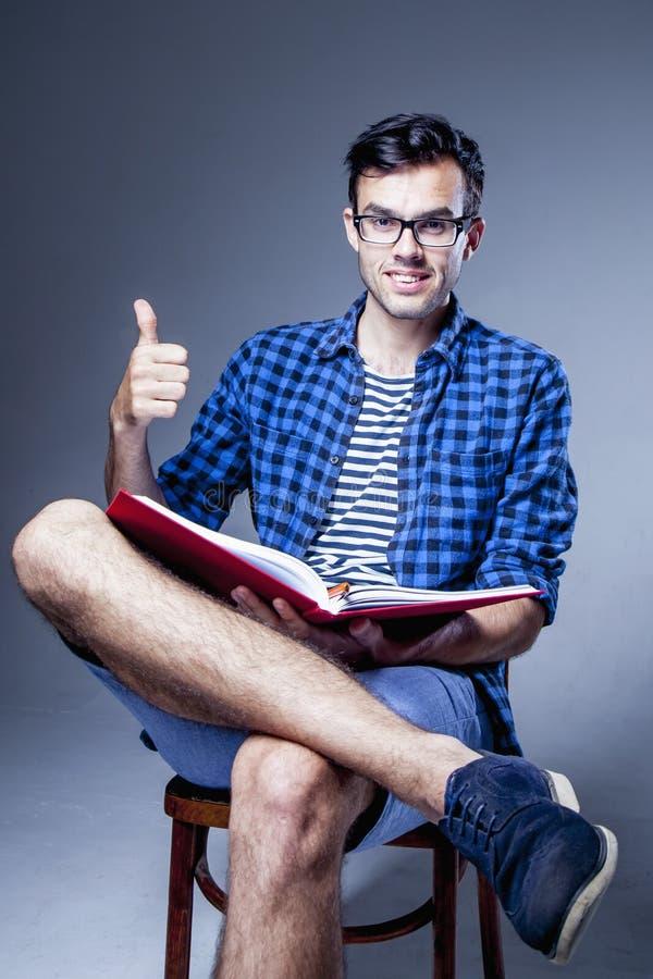 Όμορφο άτομο με το βιβλίο ανάγνωσης γενειάδων ως σύμβολο της δυνατότητας να αναληφθεί η μελέτη σε μεταπτυχιακό επίπεδο στοκ φωτογραφία με δικαίωμα ελεύθερης χρήσης