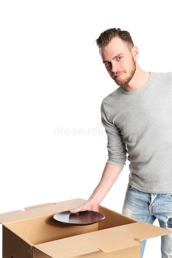 Όμορφο άτομο με το κουτί από χαρτόνι και τα πιάτα στοκ εικόνες
