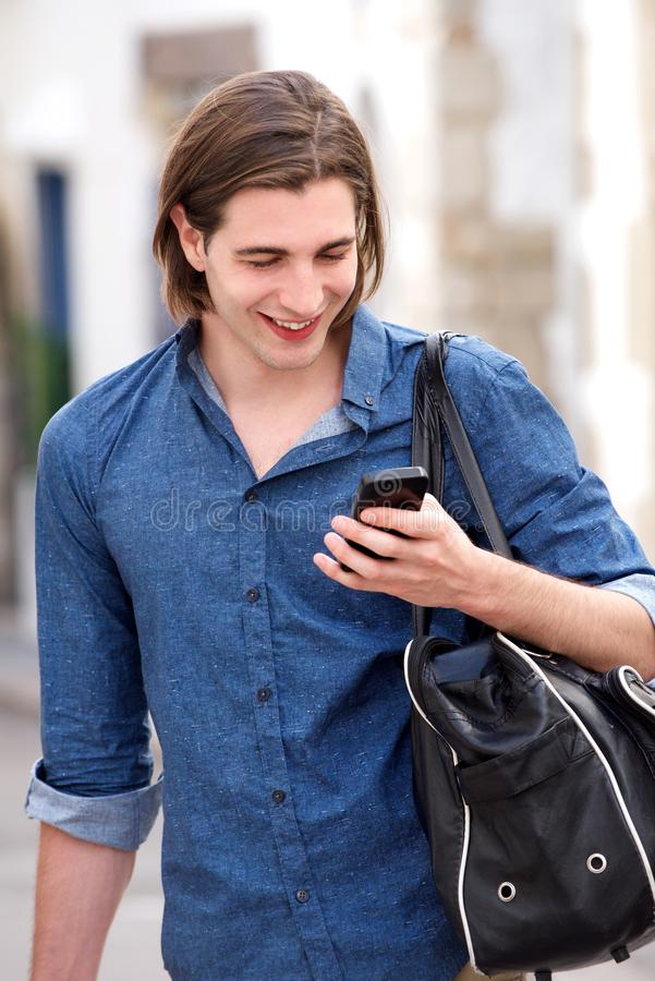 Όμορφο άτομο με το μακρυμάλλεις έξυπνες τηλέφωνο και την τσάντα εκμετάλλευσης στοκ εικόνες