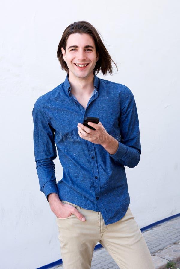 Όμορφο άτομο με το μακρυμάλλες έξυπνο τηλέφωνο εκμετάλλευσης στοκ εικόνα με δικαίωμα ελεύθερης χρήσης