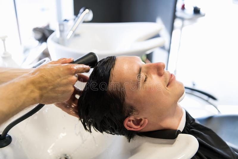 Όμορφο άτομο που έχει την τρίχα του πλυμένη hairdressing στην αίθουσα Νεαρός άνδρας που εναπόκειται στις προσοχές του ιδιαίτερες  στοκ εικόνα