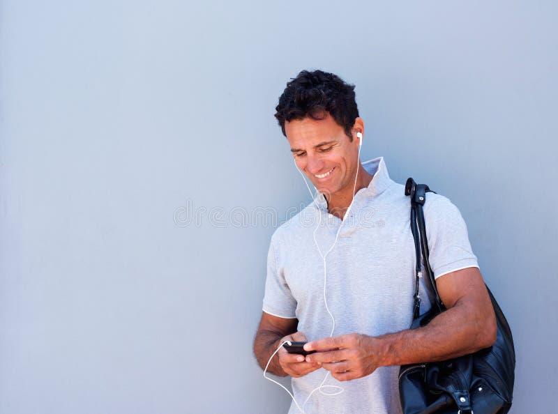 Όμορφο άτομο που ακούει τη μουσική με το κινητό τηλέφωνο στοκ εικόνες