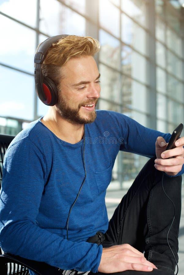 Όμορφο άτομο που ακούει τη μουσική στο έξυπνο τηλέφωνο στοκ εικόνα