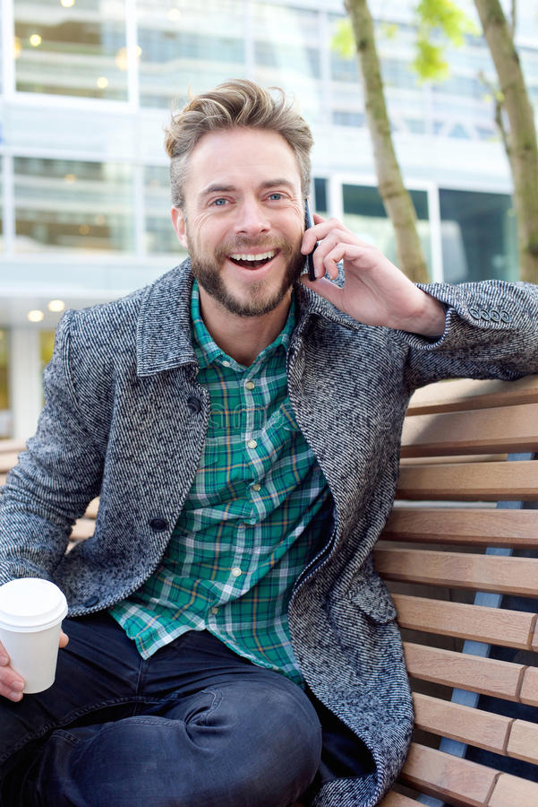 Όμορφο άτομο που γελά και που ακούει το τηλέφωνο κυττάρων έξω στοκ εικόνες