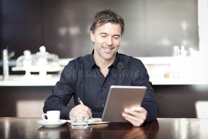 Όμορφο άτομο που γράφει στη καφετερία χρησιμοποίηση υπολογιστών στοκ εικόνες με δικαίωμα ελεύθερης χρήσης