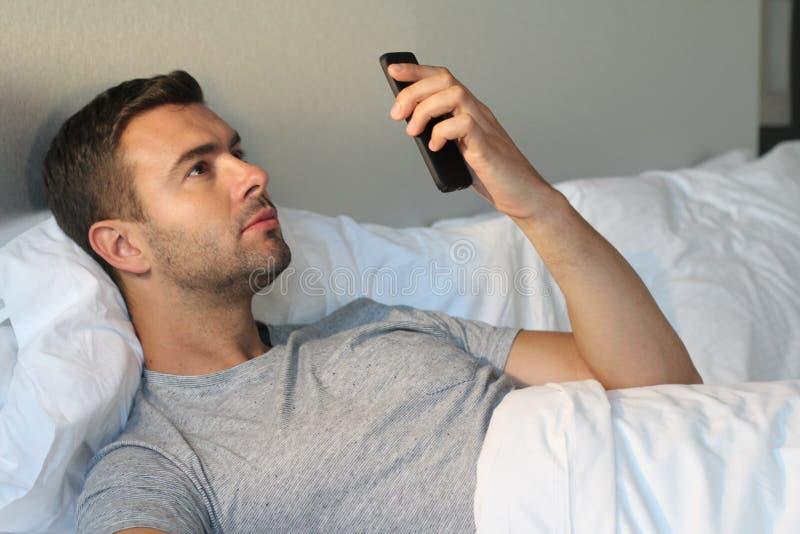 Όμορφο άτομο που εξετάζει το τηλέφωνο στο κρεβάτι στοκ φωτογραφία με δικαίωμα ελεύθερης χρήσης