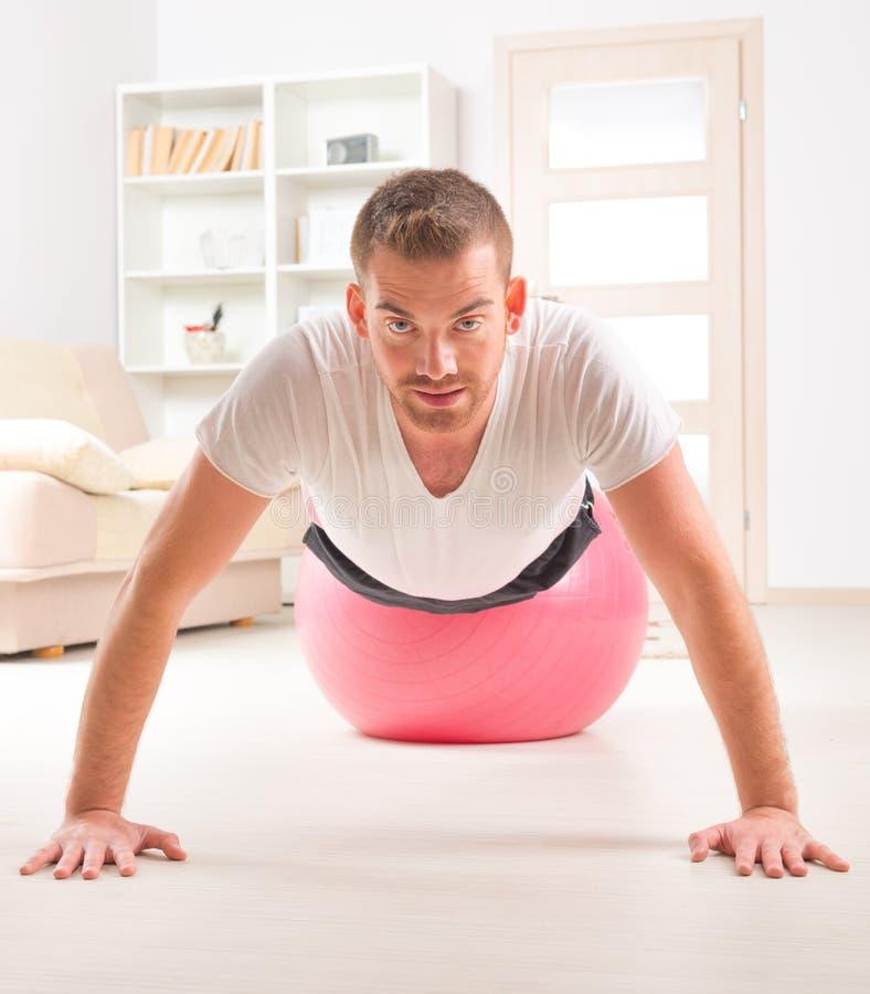 Όμορφο άτομο που κάνει την ώθηση UPS στη σφαίρα γυμναστικής στοκ φωτογραφία με δικαίωμα ελεύθερης χρήσης