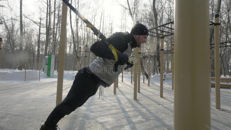 Όμορφο άτομο που κάνει workout την άσκηση με τον αποσυμπιεστή ικανότητας στο χώρο αθλήσεων στοκ εικόνα