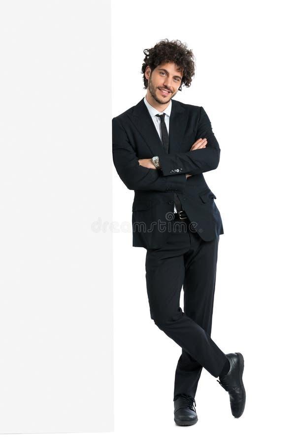 Όμορφο άτομο που κλίνει στον πίνακα διαφημίσεων στοκ εικόνες