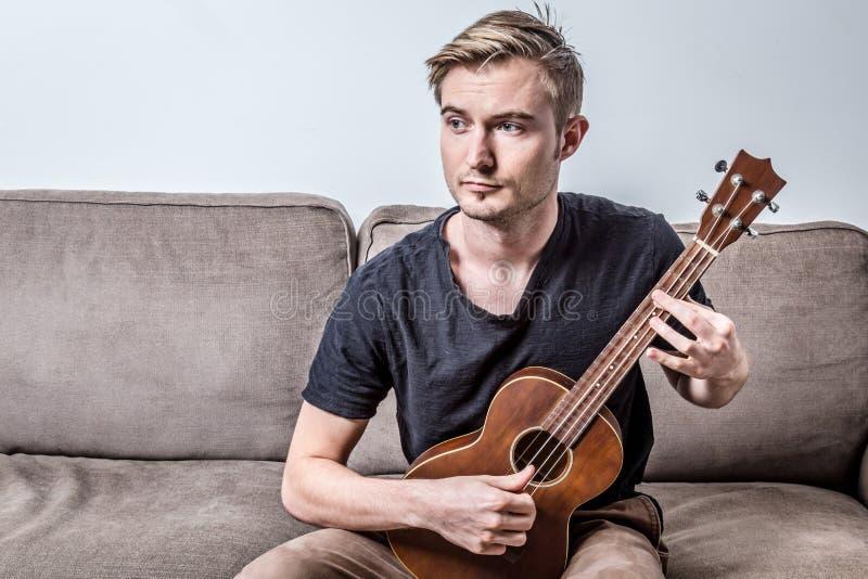 Όμορφο άτομο που παίζει ukulele ή μικρή κιθάρα με το συναίσθημα ανησυχίας στοκ φωτογραφία με δικαίωμα ελεύθερης χρήσης