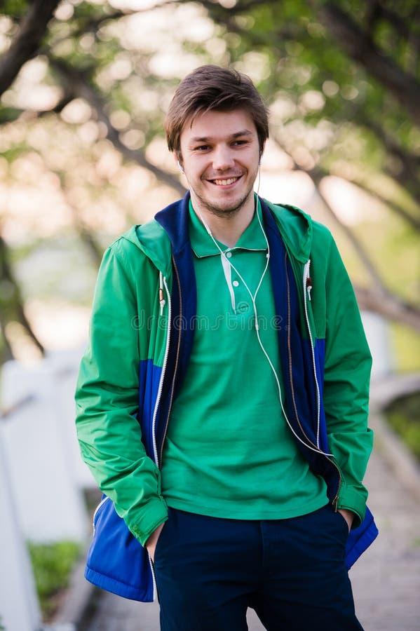 Όμορφο άτομο που περπατά γύρω από την πόλη που χαμογελά και που ακούει στη μουσική στο πάρκο Μαλακό φως ηλιοβασιλέματος στοκ φωτογραφία με δικαίωμα ελεύθερης χρήσης