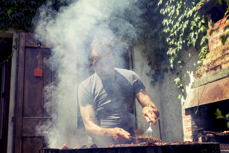 Όμορφο άτομο που προετοιμάζει το ψημένο στη σχάρα κρέας στοκ εικόνα με δικαίωμα ελεύθερης χρήσης