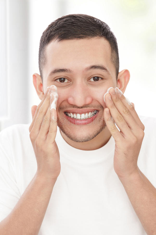 Όμορφο άτομο που πλένει το πρόσωπό του που χρησιμοποιεί τον του προσώπου αφρό στοκ φωτογραφία