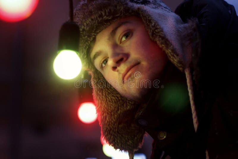 Όμορφο άτομο που στέκεται κάτω από τους αναδρομικούς βολβούς φω'των γιρλαντών στην οδό στοκ φωτογραφία με δικαίωμα ελεύθερης χρήσης