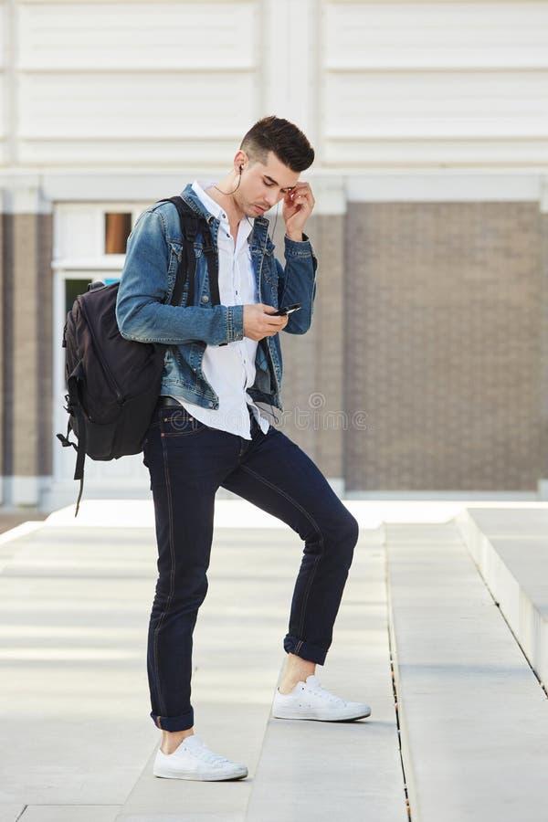 Όμορφο άτομο που στέκεται στα βήματα με την τσάντα και τα ακουστικά στοκ εικόνες με δικαίωμα ελεύθερης χρήσης