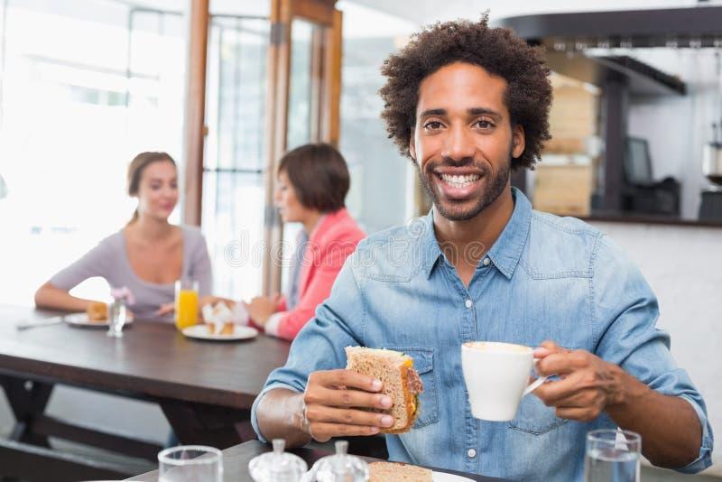 Όμορφο άτομο που τρώει ένα σάντουιτς στοκ εικόνα