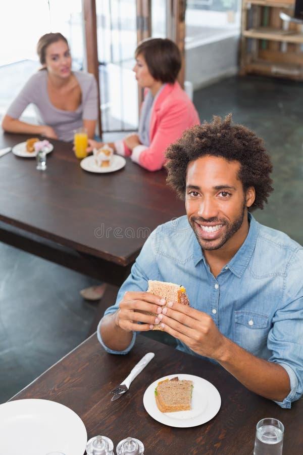 Όμορφο άτομο που τρώει ένα σάντουιτς στοκ εικόνες