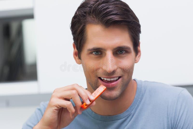 Όμορφο άτομο που τρώει μια φέτα του πιπεριού κουδουνιών στοκ φωτογραφία