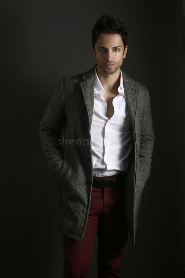 Όμορφο άτομο που φορά ένα γκρίζο παλτό στοκ φωτογραφία