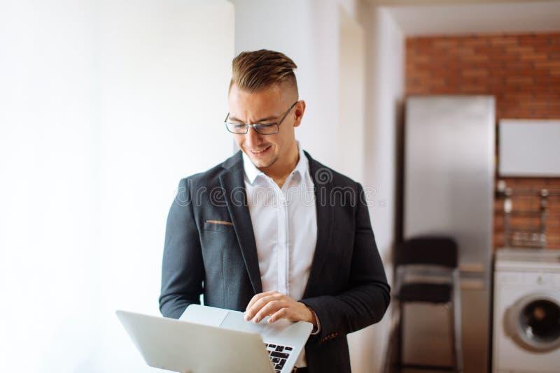 Όμορφο άτομο που φορά τα γυαλιά που λειτουργούν με το lap-top στην αρχή στοκ φωτογραφία με δικαίωμα ελεύθερης χρήσης