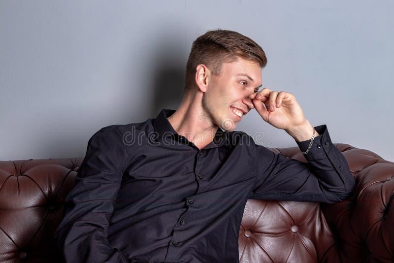 Όμορφο άτομο που φορά τη μαύρη συνεδρίαση πουκάμισων στον καναπέ δέρματος Άνεση και χαλάρωση στοκ φωτογραφία με δικαίωμα ελεύθερης χρήσης