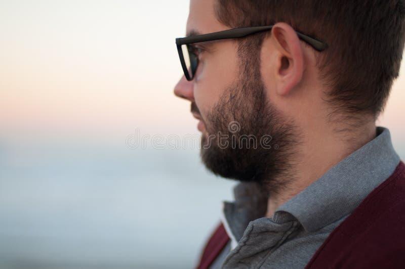 Όμορφο άτομο που φορά το πουλόβερ, αρσενικό που εξετάζει σκεπτικό την ωκεάνια θάλασσα στοκ εικόνα με δικαίωμα ελεύθερης χρήσης
