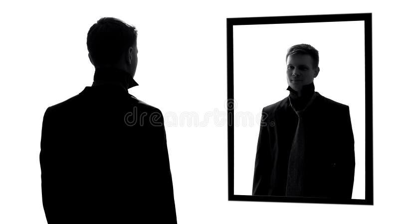 Όμορφο άτομο που φορούν το κοστούμι και δεσμός που φαίνεται καθρέφτης, βέβαια αρσενική αντανάκλαση στοκ εικόνα
