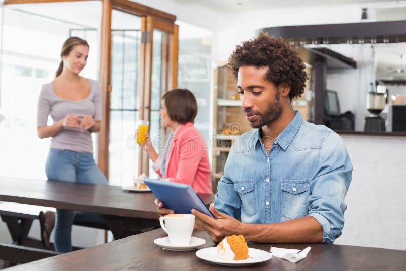 Όμορφο άτομο που χρησιμοποιεί την ταμπλέτα ενώ έχοντας τον καφέ στοκ φωτογραφία με δικαίωμα ελεύθερης χρήσης