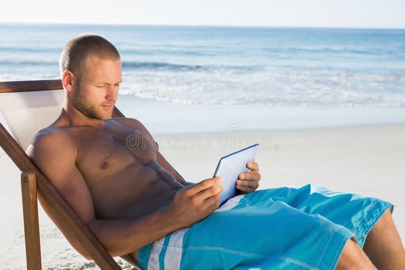 Όμορφο άτομο που χρησιμοποιεί την ταμπλέτα του κάνοντας ηλιοθεραπεία στοκ εικόνες