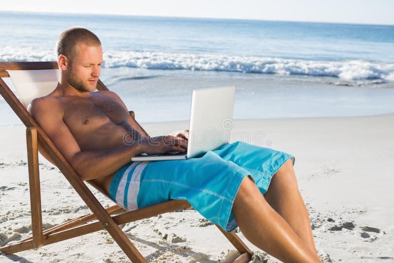 Όμορφο άτομο που χρησιμοποιεί το lap-top του χαλαρώνοντας στην καρέκλα γεφυρών του στοκ φωτογραφία με δικαίωμα ελεύθερης χρήσης