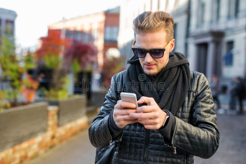 Όμορφο άτομο που χρησιμοποιεί το smartphone του στοκ εικόνες