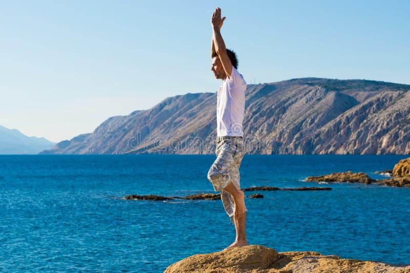 Όμορφο άτομο σε μια θέση γιόγκας στην παραλία στοκ φωτογραφία με δικαίωμα ελεύθερης χρήσης