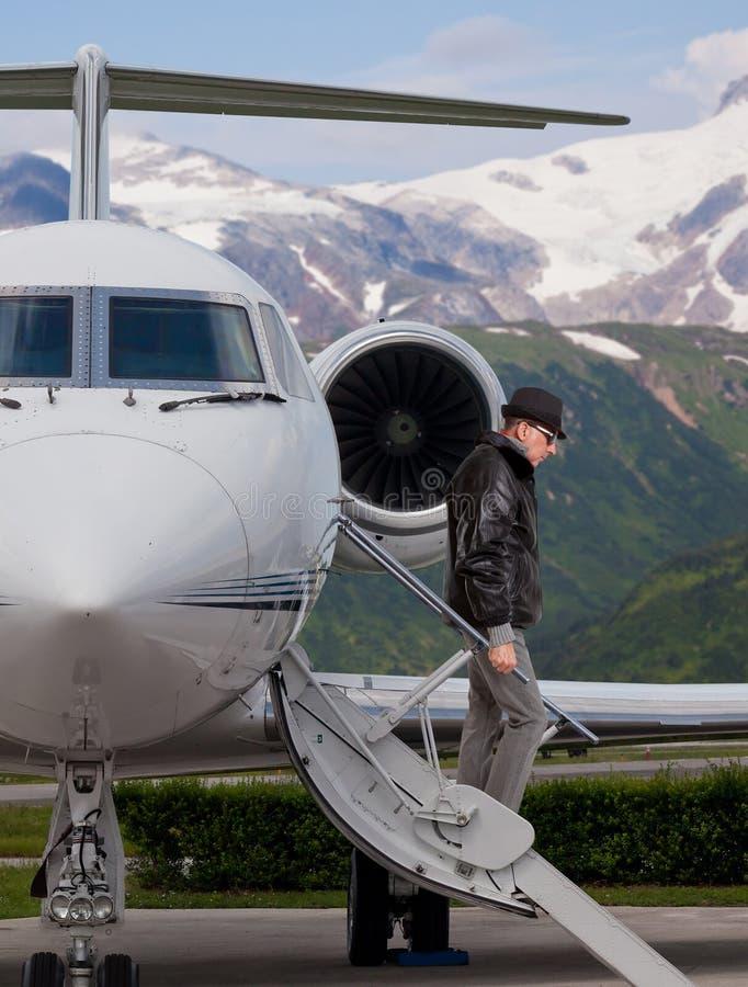 Όμορφο άτομο στα βήματα ενός ιδιωτικού αεριωθούμενου αεροπλάνου στοκ εικόνες