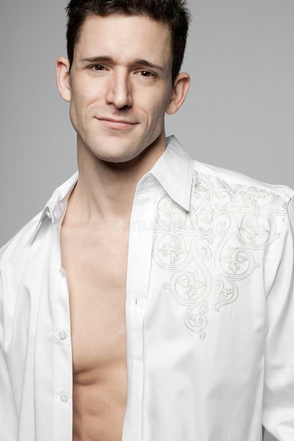 Όμορφο άτομο στο άσπρο πουκάμισο σε γκρίζο. στοκ εικόνα