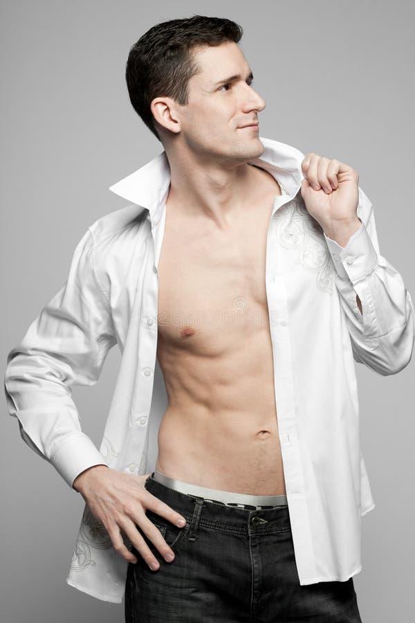 Όμορφο άτομο στο άσπρο πουκάμισο σε γκρίζο. στοκ φωτογραφία