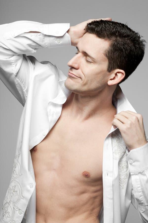 Όμορφο άτομο στο άσπρο πουκάμισο σε γκρίζο. στοκ φωτογραφία με δικαίωμα ελεύθερης χρήσης