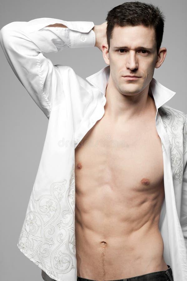 Όμορφο άτομο στο άσπρο πουκάμισο σε γκρίζο. στοκ εικόνα με δικαίωμα ελεύθερης χρήσης
