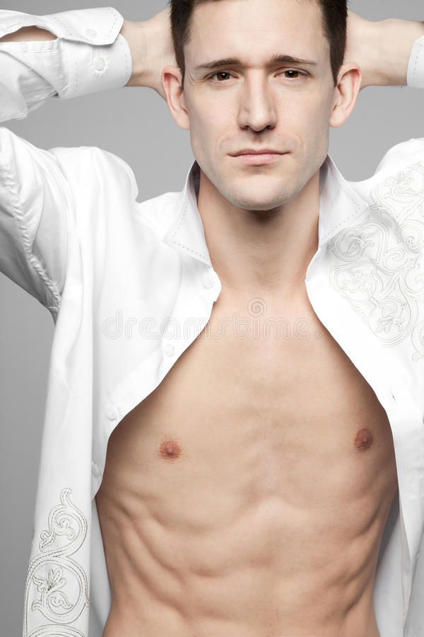 Όμορφο άτομο στο άσπρο πουκάμισο σε γκρίζο. στοκ εικόνες