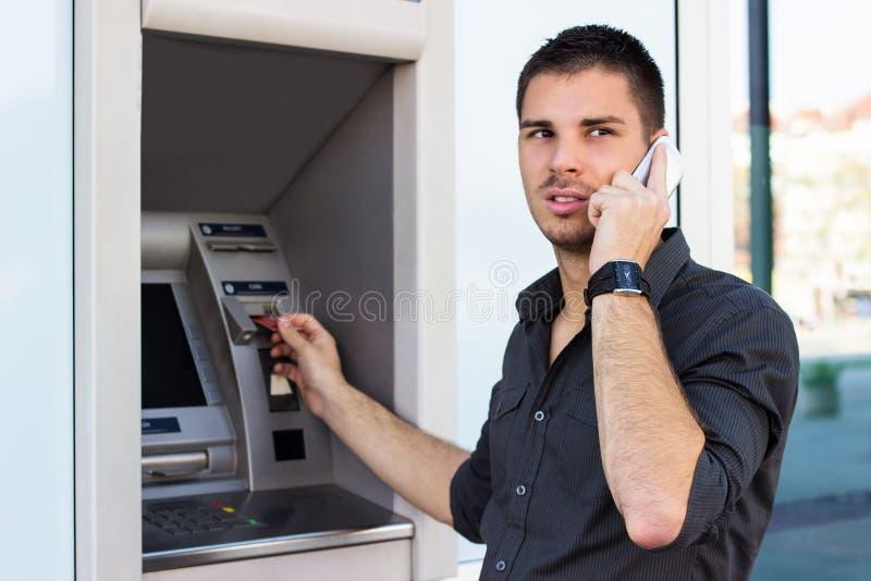 Όμορφο άτομο στο τηλέφωνο στο ATM στοκ φωτογραφίες με δικαίωμα ελεύθερης χρήσης