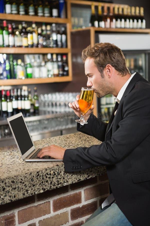 Όμορφο άτομο χρησιμοποιώντας το φορητό προσωπικό υπολογιστή και πίνοντας μια μπύρα στοκ φωτογραφία