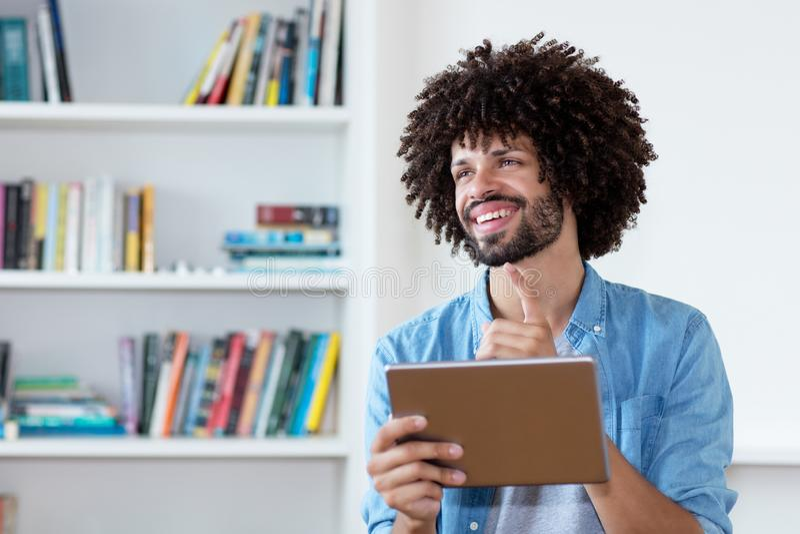 Όμορφο άτομο hipster με την τρίχα afro και τον υπολογιστή ταμπλετών στοκ φωτογραφία
