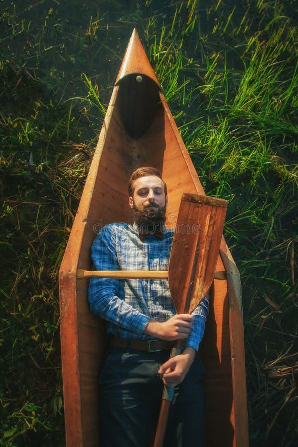Όμορφο άτομο Portrair που εναπόκειται στο κουπί στο κανό στοκ φωτογραφίες