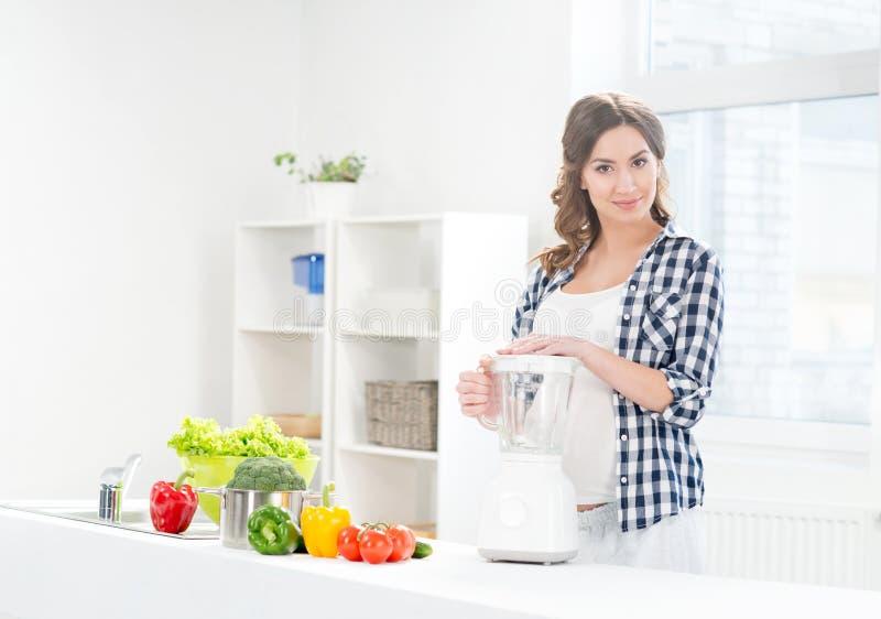 Όμορφο έγκυο μαγείρεμα γυναικών χαμόγελου με ένα μπλέντερ στοκ εικόνες