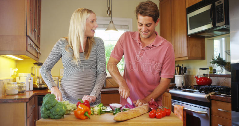 Όμορφο έγκυο μαγείρεμα ζευγών στην κουζίνα στοκ φωτογραφία με δικαίωμα ελεύθερης χρήσης