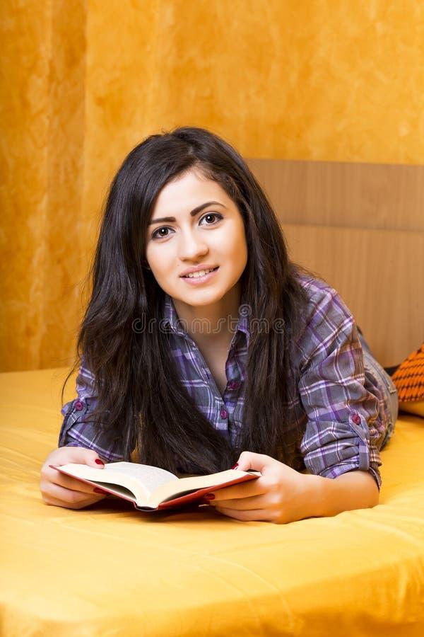 Όμορφο έφηβη που βρίσκεται στο κρεβάτι και που διαβάζει ένα βιβλίο στοκ εικόνες με δικαίωμα ελεύθερης χρήσης