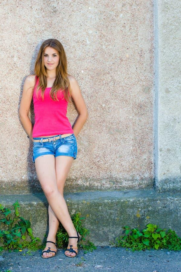 Όμορφο έφηβη που στέκεται στο συμπαγή τοίχο στο διάστημα αντιγράφων θερινής ημέρας στοκ φωτογραφίες