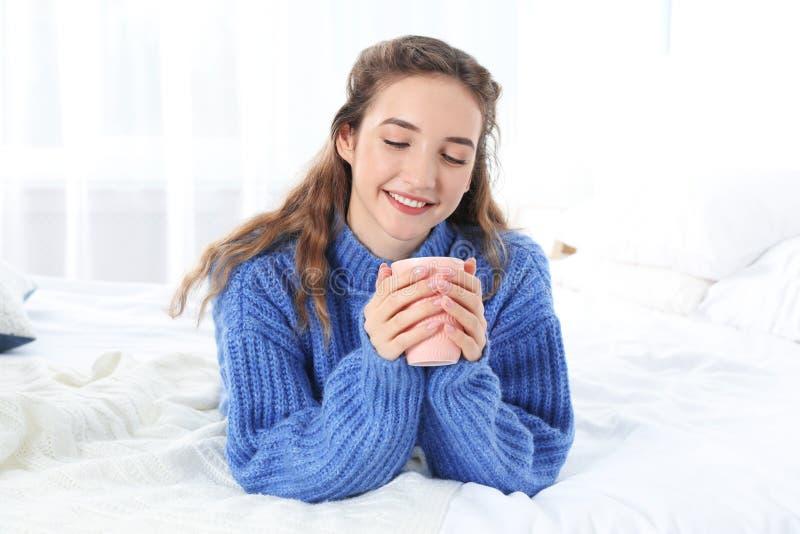 Όμορφο έφηβη στο θερμό άνετο πουλόβερ με το φλυτζάνι του ζεστού ποτού στο κρεβάτι στοκ εικόνες